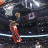 Photo - Washington Wizards' John Wall scores as Toronto Raptors' Kyle Lowry looks on during first half NBA basketball action in Toronto, Thursday, Feb. 27, 2014. (AP Photo/The Canadian Press, Chris Young)