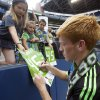 Photo - Seattle Sounders' Xander Bailey signs autographs for fans following a friendly soccer match against Tottenham Hotspur in Seattle, Saturday, July 19, 2014. The matched ended in a 3-3 draw. Bailey was signed to the Sounders for the match as part of the Make-A-Wish program. (AP Photo/Stephen Brashear)
