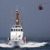 CORRECTS DATE OF CRASH TO SUNDAY, NOT MONDAY - In this Aug. 29, 2011 photo provided by the U.S. Coast Guard, a Rescue Helicopter from Airs Station Los Angeles conducts a close fly-by of the Coast Guard Cutter Halibut. A smuggler\'s vessel rammed a small U.S. Coast Guard boat deployed by the cutter Halibut, off the Southern California coast early Sunday Dec. 2, 2012, killing one Coast Guard member and injuring another, authorities said. The cutter was conducting an investigation into suspected smuggling near the Channel Islands west of Malibu. (AP Photo/U.S. Coast Guard/Steve Lee)