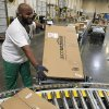 Photo - FILE - In this Nov. 11, 2010 file photo, Leacroft Green places a package on the belt at an Amazon.com fulfillment center, in Goodyear, Ariz. Amazon is teaming up with the U.S. Postal Service to deliver packages on Sundays. The Seattle company said Monday, Nov. 11, 2013, that  Sunday delivery will be available this week to customers in the New York and Los Angeles metropolitan areas. Amazon and the Postal Service plan to roll out service to