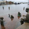 Bronze sculptures of the Kunta Kinte-Alex Haley Memorial recline in the flood waters in downtown Annapolis, Md. on Tuesday, Oct. 30, 2012. High tide swept over the banks of the city dock flooding lower Annapolis stores. The memorial features a sculpture of a seated Alex Haley (R) reading from a book on his lap to three children of different ethnic backgrounds. (AP Photo/Blake Sell)