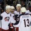 Photo - Columbus Blue Jackets' Jack Johnson, left, celebrates with James Wisniewski, center, and Brandon Dubinsky, right, as Cam Atkinson (13) joins in after Dubinsky scored the only goal of the second period of an NHL hockey game against the Buffalo Sabres in Buffalo, N.Y., Saturday, Jan.18, 2014. (AP Photo/Gary Wiepert)