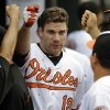 Photo - FILE - In this July 11, 2013 file photo, Baltimore Orioles' Chris Davis, center, is greeted by teammates in the dugout after hitting a solo home run in the second inning of a baseball game against the Texas Rangers in Baltimore. (AP Photo/Patrick Semansky, File)