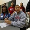 Jordan Evans, son of University of Oklahoma former defensive lineman Scott Evans, signs a letter of intent to play for OU at a signing day assembly at Norman North High School on Wednesday, Feb. 6, 2013, in Norman, Okla. Mother Tenika and sisters Jacie, 12, and Jessiika, 11, right, are with him. Photo by Steve Sisney, The Oklahoman