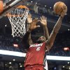 Miami Heat\'s LeBron James scores on Toronto Raptors\' Amir Johnson during first half NBA basketball action in Toronto on Sunday, March 17, 2013. (AP Photo/THE CANADIAN PRESS,Chris Young)