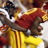 ISU\'s Jacques Washington (10) intercepts a pass by OSU\'s Brandon Weeden (not pictured) as Justin Blackmon (81) tackles Washington in the first quarter during a college football game between the Oklahoma State University Cowboys (OSU) and the Iowa State University Cyclones (ISU) at Jack Trice Stadium in Ames, Iowa, Friday, Nov. 18, 2011. Photo by Nate Billings, The Oklahoman