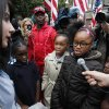 Photo -   Samantha Pawlucy, left, listens to a group of cousins recite the Declaration of Independence during a rally in support of her as she returned to school on Tuesday, Oct. 9, 2012 in Philadelphia. The young girls from left are Amerie Harris, 9, La'Joir Coppock, 8, Laija Coppock, 10, and Amani Harris, 9. They were accompanied by their grandfather, in red, background center, Lewis Harris. Pawlucy had stayed home after she was allegedly singled out by a teacher for wearing a Mitt Romney t-shirt to school. THE EVENING BULLETIN OUT, TV OUT; MAGS OUT; NO SALES