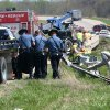 In a Sunday, April 1, 2012 photo, authorities remove victims at the scene of a deadly crash, near Williamsburg, Kan. Police said a box truck, which had living quarters inside, was pulling a trailer when it crashed into a ravine after it hit a guardrail and a concrete bridge, killing 5 of the 18 people that were inside the vehicle. A family friend said a Minnesota family and some friends were taking a spring break vacation to see a motocross race. (AP Photo/The Ottawa Herald, Jeanny Sharp) NO SALES