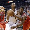 Photo - Miami Heat's Chris Bosh (1) drives to the basket as Chicago Bulls' Jimmy Butler, right, defends during the first half of Game 5 of an NBA basketball Eastern Conference semifinal, Wednesday, May 15, 2013 in Miami. At left is Bulls' Carlos Boozer. (AP Photo/Wilfredo Lee)