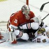 Photo - Chicago Blackhawks center Jonathan Toews (19) crashes into Detroit Red Wings goalie Jimmy Howard (35) during the second period in Game 4 of the Western Conference semifinals in the NHL hockey Stanley Cup playoffs in Detroit, Thursday, May 23, 2013. (AP Photo/Paul Sancya)