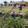 A pair of volunteers from the Pentecostal Church of God in Tecumseh, cut and stack the branches of this large tree that was knocked down by the force of Monday night\'s tornado that struck the Pottawatomie County community. Photo by Jim Beckel, The Oklahoman