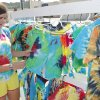 Photo - Abby Lange, 15, displays some of the tie-dyed clothing she makes and sells at the Junior Market at Edmond's Festival Market Place. Photos By David McDaniel, The Oklahoman