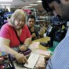 Photo - Elizabeth Dillard, left, of Oklahoma City, shows store clerk Mobi, right, the numbers she wants in the Powerball Lottery as she purchases tickets in Oklahoma City, Friday, May 17, 2013. Looking on at center is Lindsay Horn. (AP Photo/Sue Ogrocki)