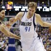 Dallas Mavericks\' Dirk Nowitzki (41), of Germany, drives by Phoenix Suns\' Luis Scola, left, of Argentina, during the second half of an NBA basketball game, Sunday, Jan. 27, 2013, in Dallas. Nowitzki scored 18 points in his 1,000th game as the Mavericks won 110-95. (AP Photo/Tony Gutierrez)