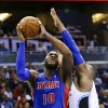Photo - Detroit Pistons' Greg Monroe (10) shoots as he gets around Orlando Magic's Glen Davis, right, during the first half of an NBA basketball game in Orlando, Fla., Friday, Dec. 27, 2013. (AP Photo/John Raoux)