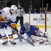 Photo - New York Rangers goalie Henrik Lundqvist, right, blocks a shot by New York Islanders' Matt Martin (17) during the first period of the NHL hockey game in New York, Thursday, Feb. 7, 2013. (AP Photo/Seth Wenig)
