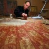 In this photo taken Friday, Feb. 8, 2013, Belarus artist Igor Arinich creates an image made of hundreds of Soviet-era banknotes in Minsk, Belarus. Arinich has used Soviet banknotes which he buys at local flea markets in Belarus for his works. (AP Photo/Sergei Grits)