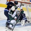 Photo - Winnipeg Jets' Adam Pardy (2) battles with Minnesota Wild's Cody McCormick (8) in front of Jets' goaltender Michael Hutchinson (34) during first period NHL hockey action in Winnipeg, Manitoba, Monday, April 7, 2014. (AP Photo/The Canadian Press, Trevor Hagan)