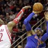 Photo - New York Knicks forward Carmelo Anthony (7) shoots over Houston Rockets center Dwight Howard (7) during the second quarter of an NBA basketball game, Friday, Jan. 3, 2014, in Houston. (AP Photo/Patric Schneider)