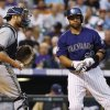 Photo - Colorado Rockies' Wilin Rosario, right, reacts after striking out as Milwaukee Brewers catcher Jonathan Lucroy heads off the field with the ball ending the fourth inning of a baseball game in Denver on Saturday, July 27, 2013. (AP Photo/David Zalubowski)