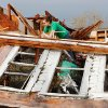 Rebecca Apel, 15, climbs on top of what remains of her family\'s home on SH 74 east of Cashion. She was looking for her birds; she located the cage and is trying to remove it from behind this toppled west wall of the house. Her home was demolshed when a tornado came through the area lateTuesday afternoon, May 24, 2011, Photo by Jim Beckel, The Oklahoman