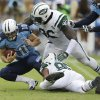 Photo - New York Jets defensive end Muhammad Wilkerson (96) and Antwan Barnes (95) bring down Tennessee Titans quarterback Jake Locker (10) in the second quarter of an NFL football game on Sunday, Sept. 29, 2013, in Nashville, Tenn. (AP Photo/Wade Payne)