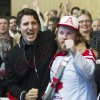 Federal Liberal leader Justin Trudeau, left, celebrates with Mike Burton as they watch team Canada beat team USA in the semifinal hockey game at the 2014 Sochi Winter Olympic Games on day two of the party\'s biennial convention in Montreal, Friday, Feb. 21, 2014. (AP Photo/The Canadian Press, Graham Hughes)