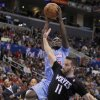 Photo - Los Angeles Clippers guard Darren Collison, left, leaps by Minnesota Timberwolves guard J.J. Barea (11) to take a shot in the first half of an NBA basketball game in Los Angeles on Sunday, Dec. 22, 2013. (AP Photo/Alex Gallardo)
