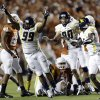 West Virginia\'s Desmond Jackson (99) celebrates with teammates after they forced Texas to miss a field goal-attempt during the fourth quarter of an NCAA college football game on Saturday, Oct. 6, 2012, in Austin, Texas. West Virginia won 48-45. (AP Photo/Eric Gay)