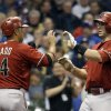 Photo - Arizona Diamondbacks' Paul Goldschmidt is congratulated by Martin Prado (14) after Goldschmidt hit a two-run home run during the third inning of a baseball game against the Milwaukee Brewers Wednesday, May 7, 2014, in Milwaukee. (AP Photo/Morry Gash)