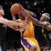 Photo -   Los Angeles Lakers guard Kobe Bryant, middle, tries to drive though Denver Nuggets' Danilo Gallinari, left, and Al Harrington during the first half of Game 2 of an NBA basketball first-round playoff series, in Los Angeles on Tuesday, May 1, 2012. (AP Photo/Chris Carlson)