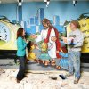 """Photo - Jennifer Grimes, children's minister at Oakcrest Church of Christ, 1111 SW 89, visits with Bob Palmer of Palmer Studios as Palmer paints a mural reflecting the church's children's ministry called """"Starting Line Kids.""""  Photos by Paul B. Southerland, THE OKLAHOMAN"""