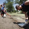 Ryan Wagner (left) and Dustin Brown use shovels to remove cut sod from the side of a green at Coffee Creek Country Club in Edmond, OK, Monday, July 18, 2011. Coffee Creek is closing for two months and installing new heat resistant grass. By Paul Hellstern, The Oklahoman