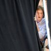 FILE - In this Wednesday, July 15, 2009 file photo Paul McCartney peeks through the curtains during rehearsals for a performance atop the Ed Sullivan Theater marquee during a taping of