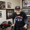 McNiece is shown in the living room of his home. On the walls behind him are various paintings and mementos associated with his military service. Jake McNiece, 93, was a paratrooper with 101st Airborne who parachuted behind enemy lines in northern France and led a team of men dubbed the