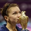 Photo - Simona Halep of Romania displays the trophy after her victory against Angelique Kerber of Germany in the final match of the Qatar WTA Ladies Open tennis tournament, in Doha, Qatar, Sunday, Feb. 16, 2014. (AP Photo/Osama Faisal)
