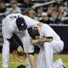 Photo -   New York Yankees' Mark Teixeira, left, checks on relief pitcher Joba Chamberlain after Chamberlain was hit by a broken bat during the twelfth inning of Game 4 of the American League division baseball series against the Baltimore Orioles, Thursday, Oct. 11, 2012, in New York. (AP Photo/Bill Kostroun)