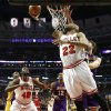 Chicago Bulls forward Taj Gibson (22) shoots a reverse layup past Los Angeles Lakers forward Pau Gasol as Bulls\' Nazr Mohammed (48) watches during the first half of an NBA basketball game, Monday, Jan. 21, 2013, in Chicago. (AP Photo/Charles Rex Arbogast)