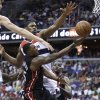 Photo - Miami Heat guard Mario Chalmers, center, drives to the basket against Washington Wizards forward Jan Vesely, left, and center Kevin Seraphin during the first half of an NBA basketball game Wednesday, April 10, 2013, in Washington. (AP Photo/Evan Vucci)