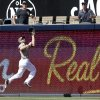 Photo - San Diego Padres right fielder Xavier Nady jumps at the fence to make the catch on a long drive hit by San Francisco Giants' Gregor Blanco in the eighth inning of a baseball game Sunday, April 20, 2014, in San Diego.  (AP Photo/Lenny Ignelzi)