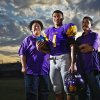 Anadarko High School football running back Sheldon Wilson holds a photo of his birth father, Clifton Wilson, as he poses for a photo with his mother LaCretia Vasquez and his mom\'s boyfriend Jose Gutierrez at the school\'s football stadium on Wednesday, Oct. 26, 2011. in Anadarko, Okla. Photo by Chris Landsberger, The Oklahoman