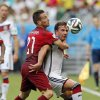 Photo - Portugal's Joao Pereira, left, challenges Germany's Mario Goetze during the group G World Cup soccer match between Germany and Portugal at the Arena Fonte Nova in Salvador, Brazil, Monday, June 16, 2014.  (AP Photo/Matthias Schrader)