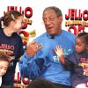 Photo - FILE - In this April 29, 1999 file photo, Bill Cosby talks with school children, from bottom left, Laura Wing, Kathryn Wing, and Aliyah Thomas at the Hasrold Washington Library in Chicago. Cosby, celebrating 25 years at pitchman for Jell-O, was on hand for the donation of his Little Bill beginner books to the library. Despite its enduring place in pop culture, Jell-O sales have tumbled 19 percent from five years ago, with alternatives such as Greek yogurt surging in popularity. (AP Photo/Stephen J. Carrera, File)