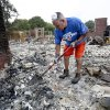 George Reich tries to salvage items after his home on Blackjack Lane was destroyed by wildfire in Edmond, Okla., Sunday, Aug. 7, 2011. A wildfire burned 1,000-acre blaze and several homes Saturday. (AP Photo/The Oklahoman, Sarah Phipps)
