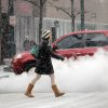 A woman crosses the street as steam rises from a manhole cover in Denver\'s financial district on Tuesday, April 9, 2013. A blizzard forecast for the area did not materialize. Instead as much as four inches of snow could fall on the Mile High City. (AP Photo/Ed Andrieski)