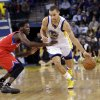 Golden State Warriors\' Stephen Curry (30) drives against Philadelphia 76ers\' Jrue Holiday (11) during the second half of an NBA basketball game in Oakland, Calif., Friday, Dec. 28, 2012. Golden State won 96-89. (AP Photo/Marcio Jose Sanchez)