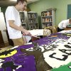 Photo - Bishop McGuinness senior Connor Ferguson works on carnival signs as part of a senior class community service project at The Sanctuary women's development center, 2133 SW 11 in Oklahoma City.  Photo by SARAH PHIPPS, The Oklahoman