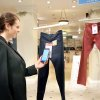 Photo - In this undated photo provided by Hointer, a woman demonstrates the Seattle store's shopping technology. Hointer displays clothing not in piles or on racks but as one piece hanging at a time, like a gallery. Shoppers just touch their smartphones to a coded tag on the item and then select a color and size via their phone. Technology in the store keeps track of the items, and by the time a shopper is ready to try them on, they're already at the dressing room. (AP Photo/Hointer)