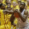 Photo - Kansas center Joel Embiid, right, fights for a rebound with Iowa State forward Melvin Ejim, left, during the first half of an NCAA college basketball game, Monday, Jan. 13, 2014, in Ames, Iowa. (AP Photo/Charlie Neibergall)