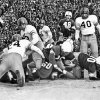 This sideline action shot shows University of Oklahoma quarterback Jack Mitchell (26) squirming through the line to score OU\'s first touchdown in the 1947 Bedlam game. Oklahoma A&M\'s Arlen McNeil (24) is poised to make the belated tackle. The Sooners beat the Cowboys 21-13 in Norman. OKLAHOMAN ARCHIVE PHOTO